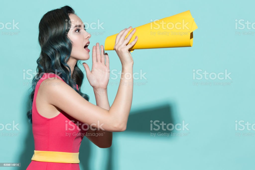 Young beautiful girl speaks in a yellow paper loudspeaker. stock photo