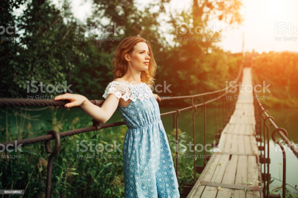 young beautiful girl standing on the bridge over the river. stock photo