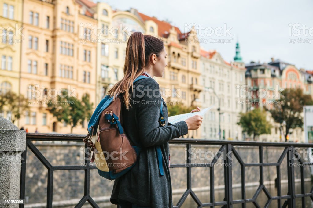 3f6c774283b9 A young beautiful girl stands and looks at the map next to the Vltava River  with the amazing old architecture of Prague in the background with a sunny  ...