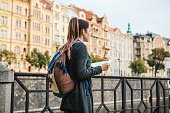 A young beautiful girl stands and looks at the map next to the Vltava River with the amazing old architecture of Prague in the background with a sunny spring day. Interesting attraction. Tourism