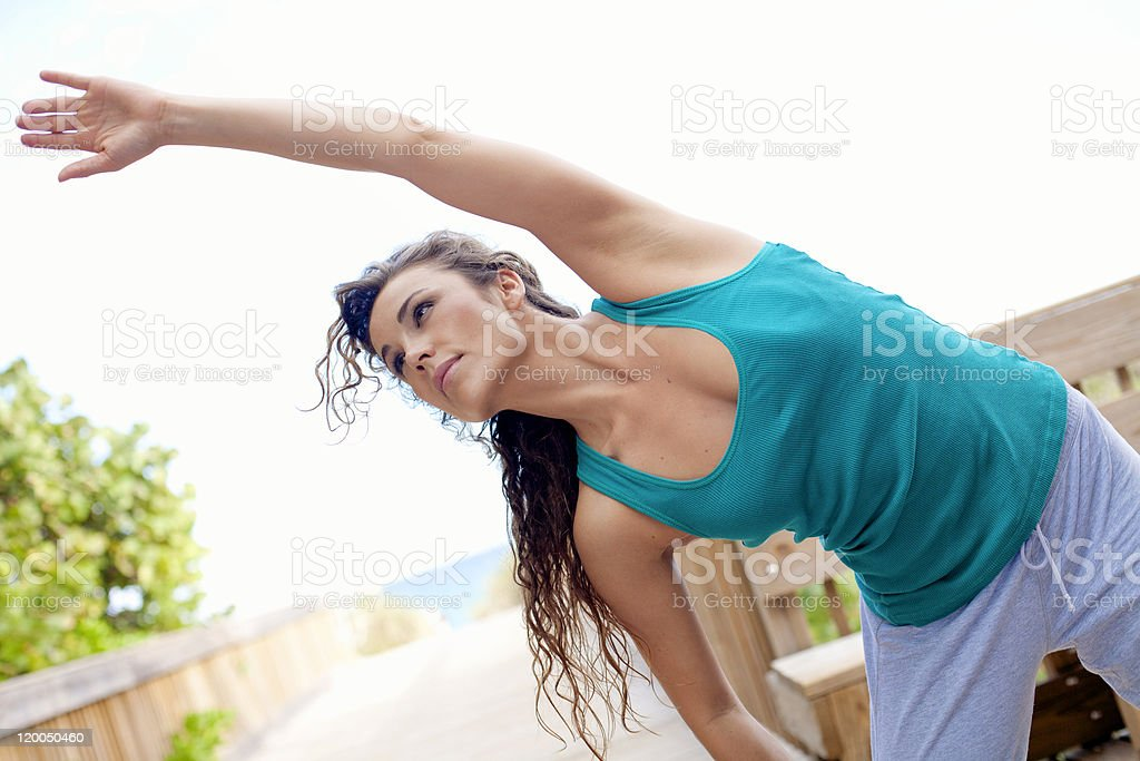 young beautiful girl stretching exercising at the beach royalty-free stock photo