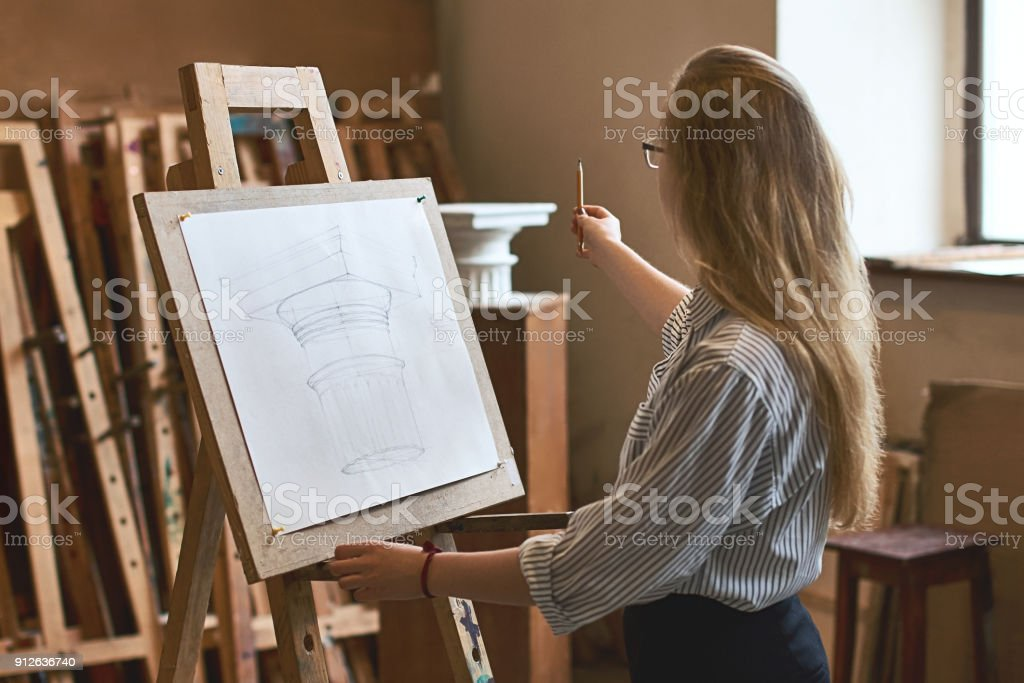 Young beautiful girl student is drawing a Doric capital with a pencil on a wooden easel as her university assignment stock photo