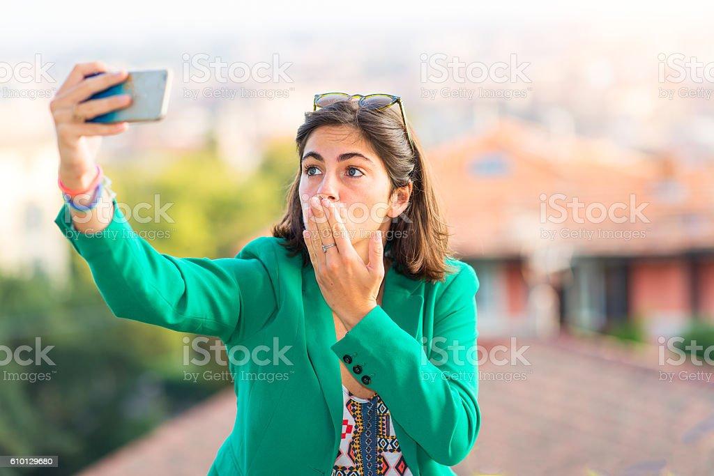 Young beautiful girl taking sends a kiss away selfies stock photo
