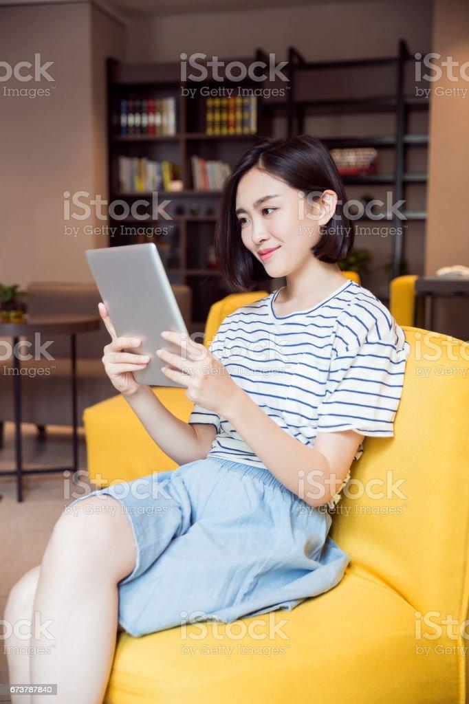 Jeune fille belle, à l'aide de tablette numérique dans la salle de séjour photo libre de droits