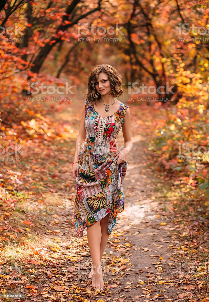 Young beautiful girl walking in autumn forest stock photo