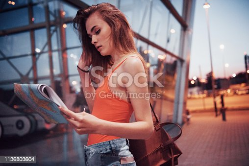 istock A young beautiful girl with a backpack behind her shoulders standing on the street near an airport. She just arrived from the rest and very happy 1136803604
