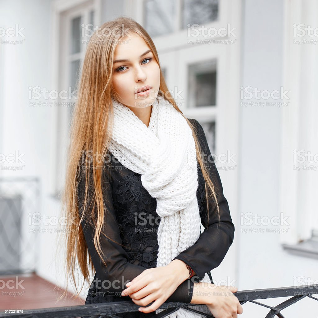 Young beautiful girl with a warm knitted scarf standing stock photo