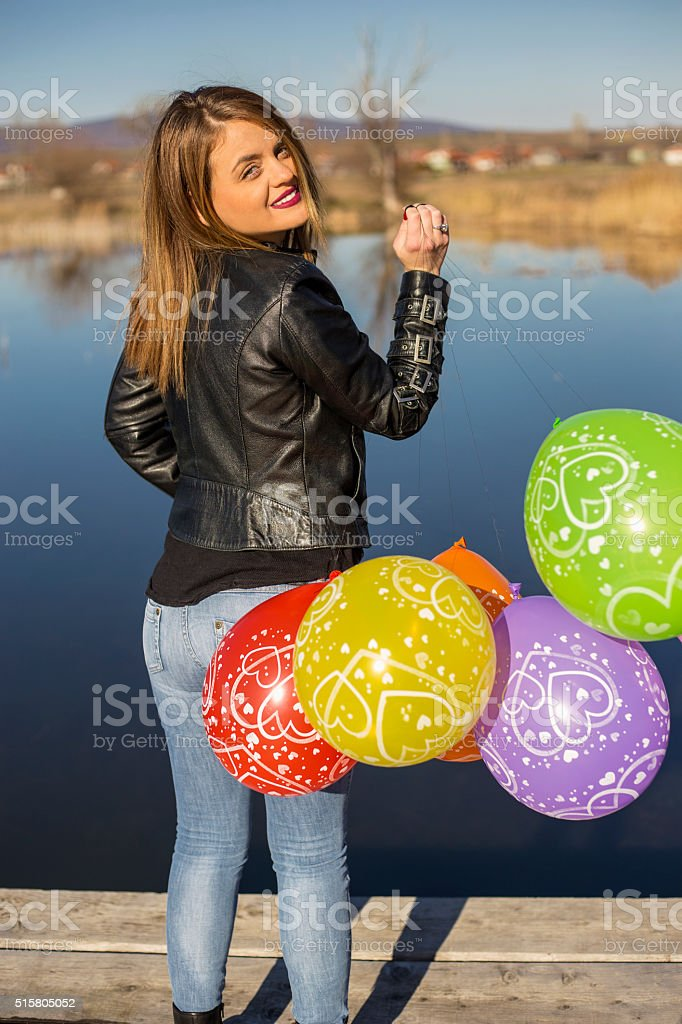Young beautiful girl with colorful ballons in the lake stock photo