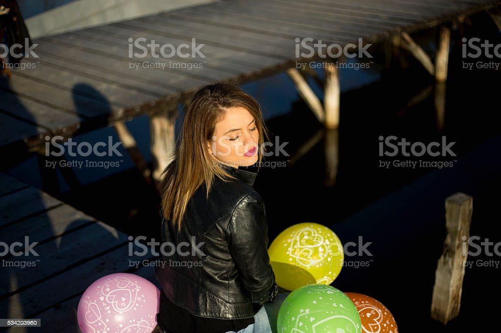 Young beautiful girl with colorful ballons on pier stock photo