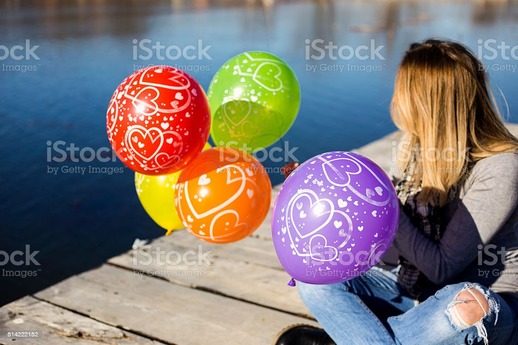 Young beautiful girl with colorful ballons on the lake stock photo