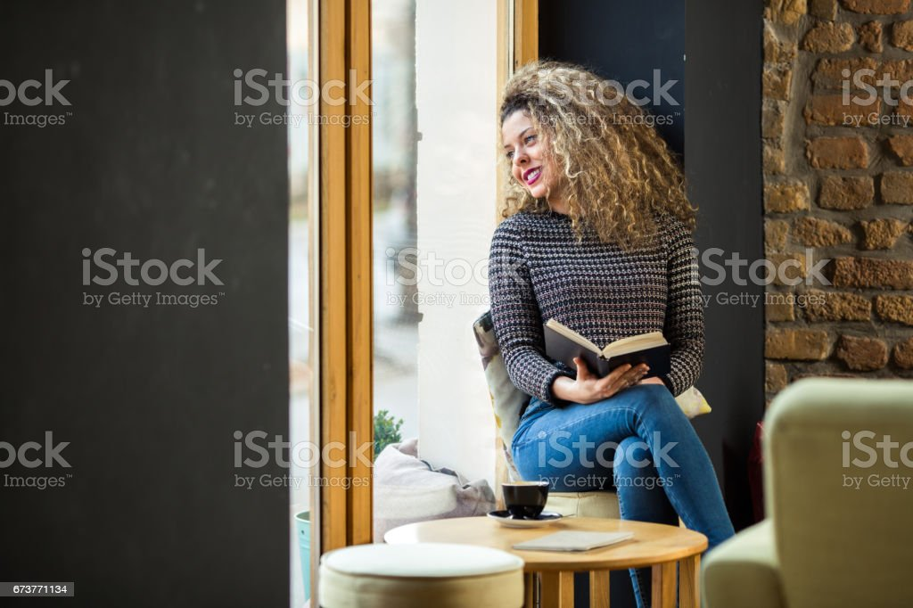 Young beautiful girl with curly hair is sitting next to cafe window and looking out. photo libre de droits