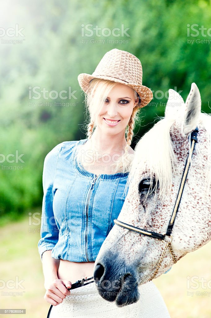 Young beautiful girl with her horse stock photo