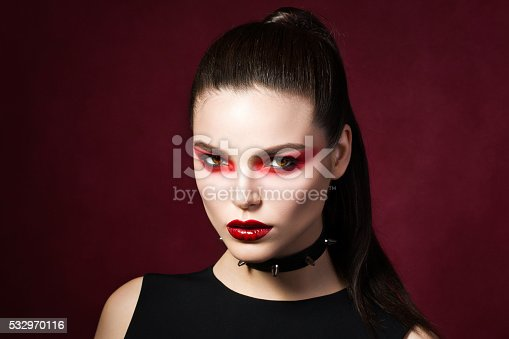 istock Young beautiful gothic woman with white skin and red lips 532970116