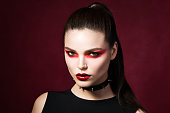 Young beautiful gothic woman with white skin and red lips with bloody drops wearing black collar with spikes. Red smokey eyes. Vampire or halloween make-up.