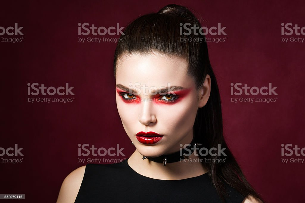 Young beautiful gothic woman with white skin and red lips stock photo