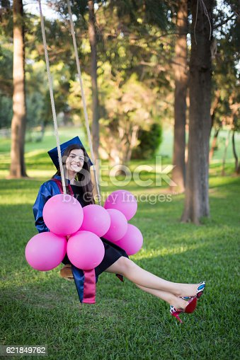 1127798356 istock photo Young beautiful graduate girl with baloons in the field 621849762