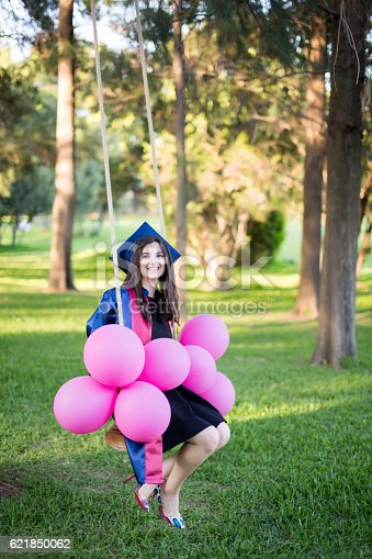1127798356 istock photo Young beautiful graduate girl with baloons in the field 621850062
