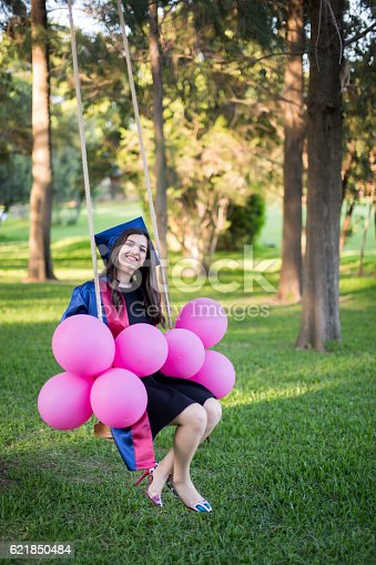 1127798356 istock photo Young beautiful graduate girl with baloons in the field 621850484