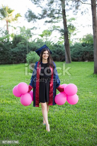 1127798356 istock photo Young beautiful graduate girl with baloons in the field 621851740