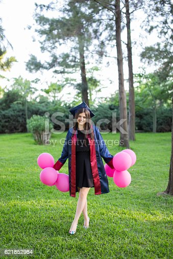 1127798356 istock photo Young beautiful graduate girl with baloons in the field 621852984