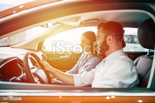 627863858istockphoto Young beautiful happy couple ride in car while travelling 1017620346