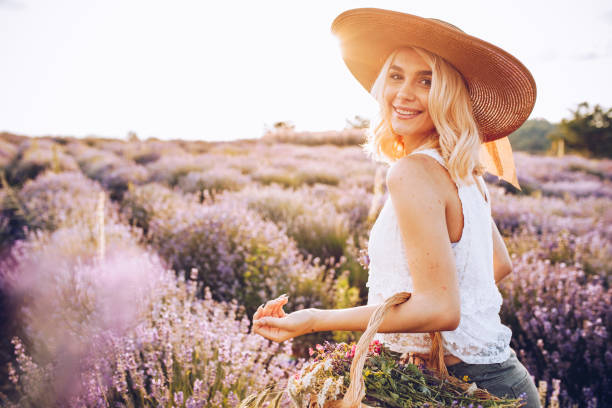 Young beautiful happy female in the lavender field stock photo