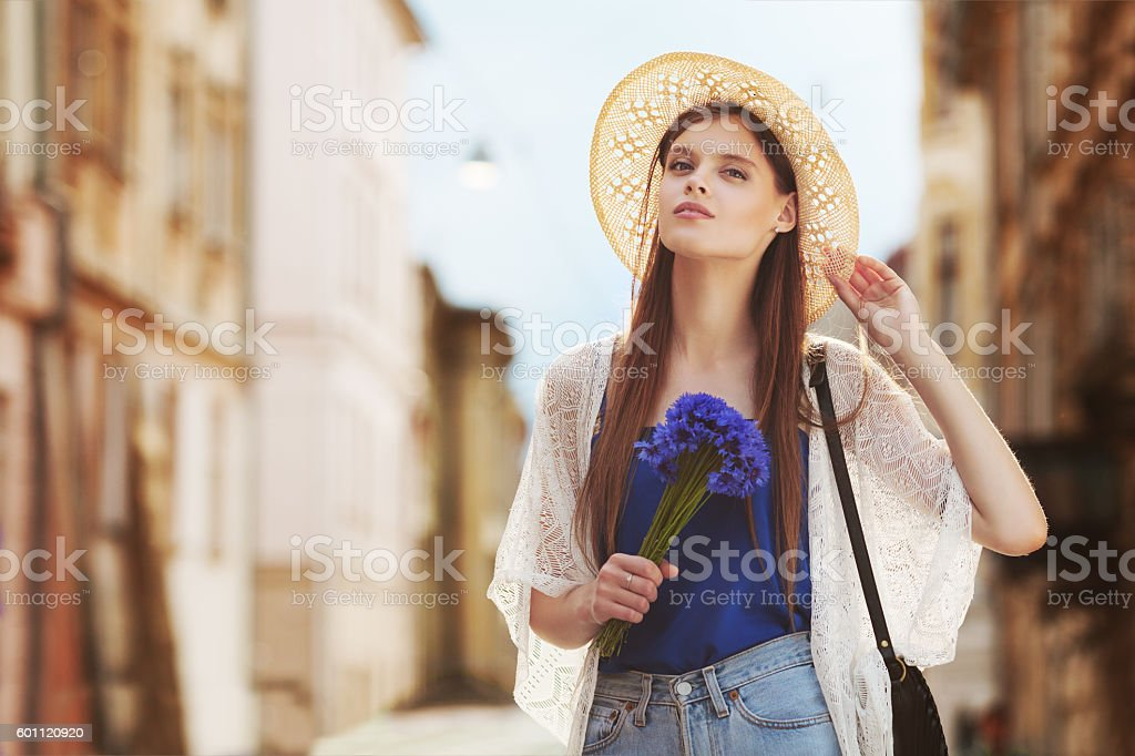 Young beautiful happy lady posing on a street. Model wearing stock photo