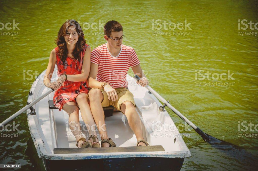 Küçük bir tekne bir gölde kürek genç güzel mutlu sevgi dolu bir çift. Eğlenceli bir doğada tarih. Bir botla sarılma bir çift. royalty-free stock photo
