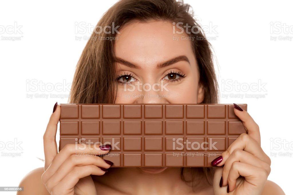 young beautiful happy woman covering half his face with a large chocolate on white background royalty-free stock photo