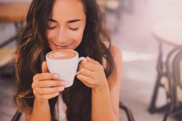 junge schöne glückliche frau genießen cappuccino in einem café - cafe stock-fotos und bilder