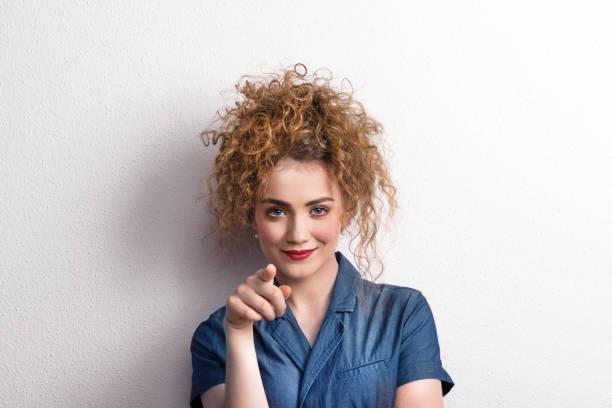 jonge mooie gelukkig woman in studio, wijzend op u. - blond curly hair stockfoto's en -beelden