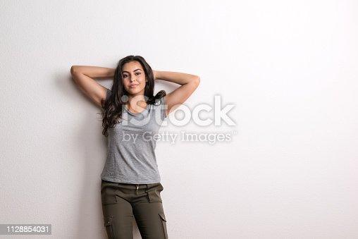Young beautiful happy woman standing in a studio in studio, hands behind her head. Copy space.