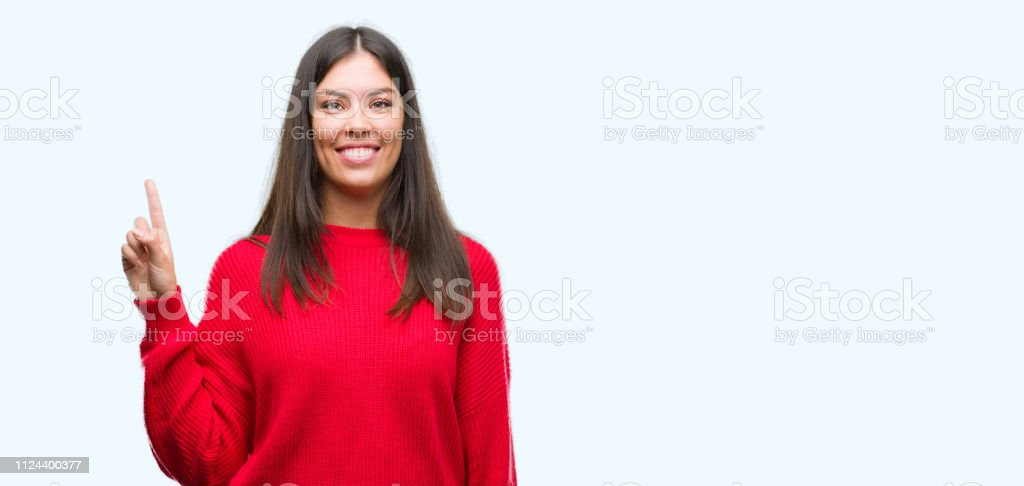 Young beautiful hispanic wearing red sweater showing and pointing up with finger number one while smiling confident and happy. stock photo