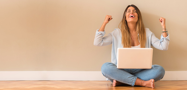 Young beautiful woman very happy sitting on the floor with computer doing winner gesture.
