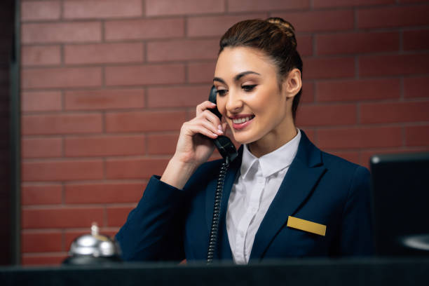 young beautiful hotel receptionist receiving call at workplace - hotel checkin foto e immagini stock