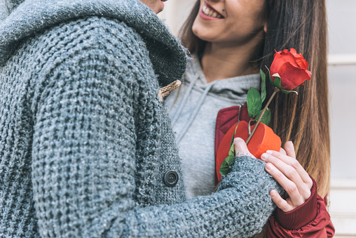 Young beautiful in love couple hugging each other in the street giving surprise gift and a red rose