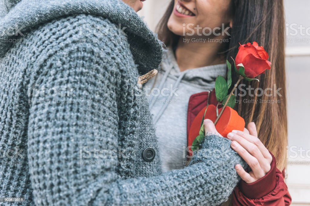 Young beautiful in love couple hugging each other in the street giving surprise gift and a red rose'n stock photo