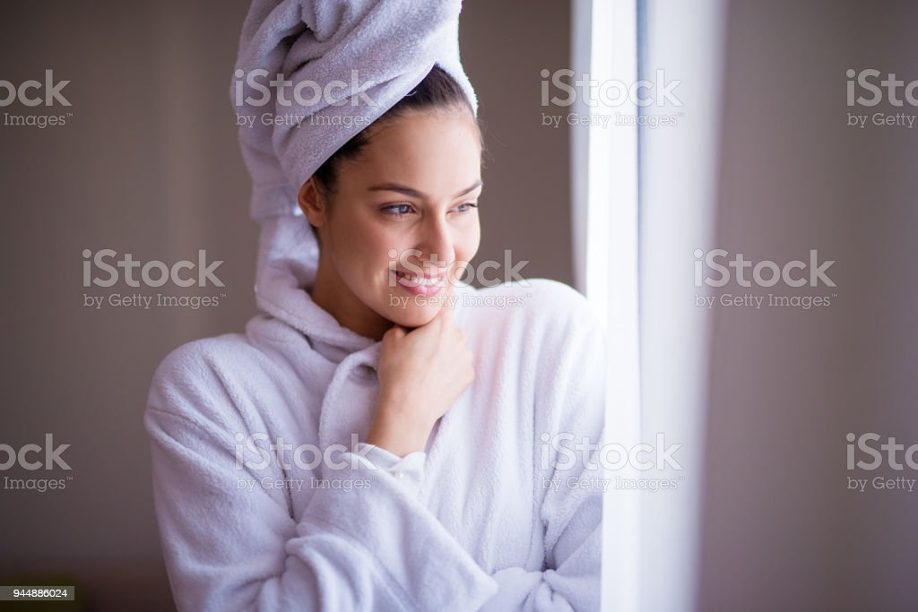 Young beautiful joyfull woman in a robe with a towel around her hair is smiling and feeling fresh after the shower while looking out of the window and feeling cozy. stock photo