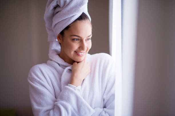 young beautiful joyfull woman in a robe with a towel around her hair is smiling and feeling fresh after the shower while looking out of the window and feeling cozy. - accappatoio foto e immagini stock