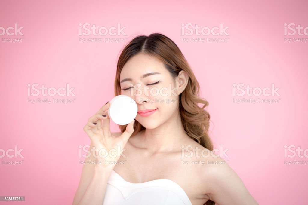 Young beautiful korea woman holding product in hand with relax emotion at pink background, 20-30 year old. stock photo
