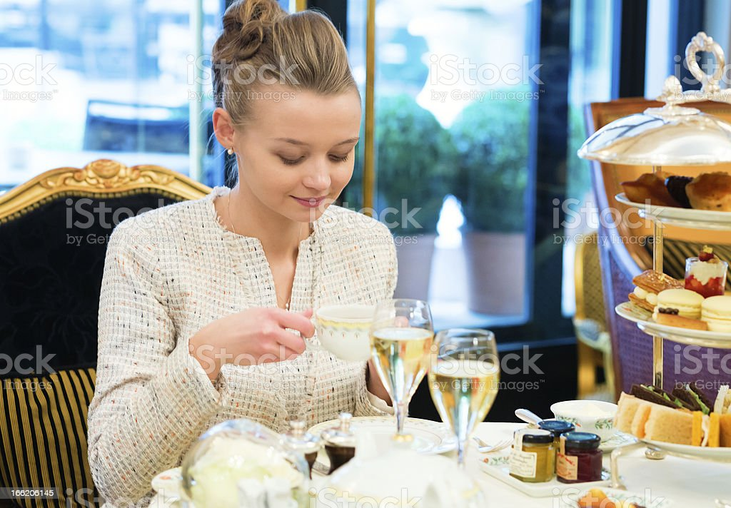 Young beautiful lady at high tea ceremony stock photo