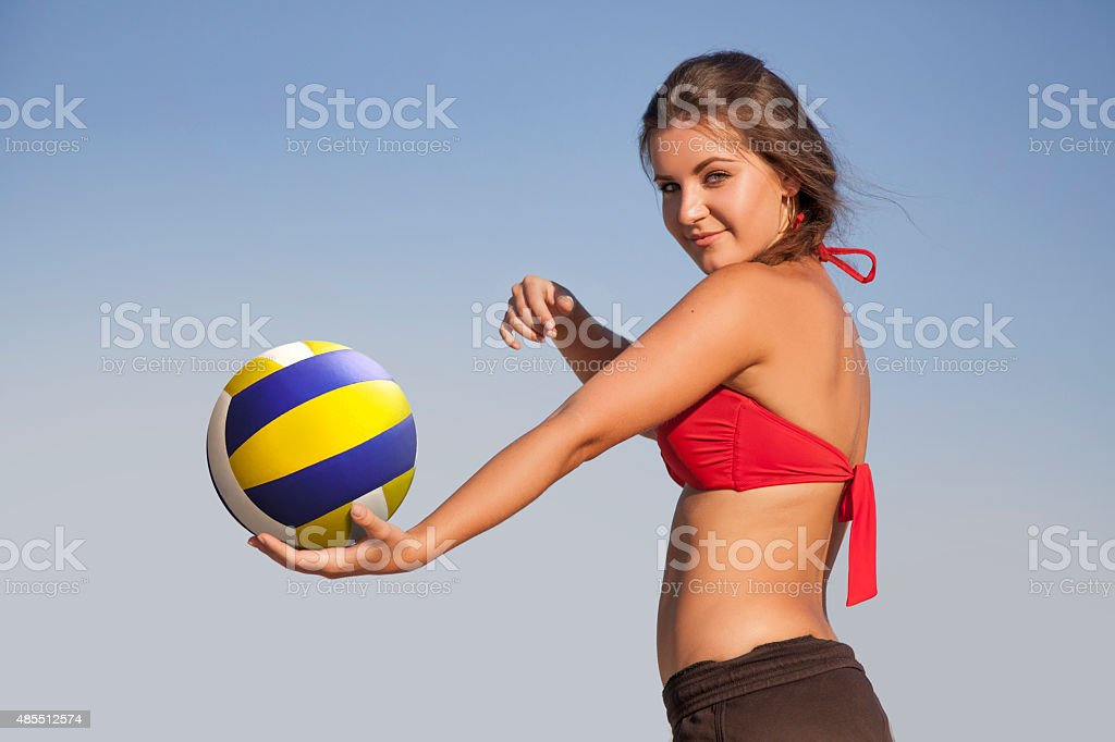 Young beautiful lady is playing volleyball on the beach stock photo