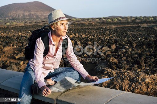 young beautiful lonely traveler woman looking at the map to choose her next destination and adventure. backpackers life and wanderlust feeling concept. cheerful nice blonde in alternative vacation lifestyle