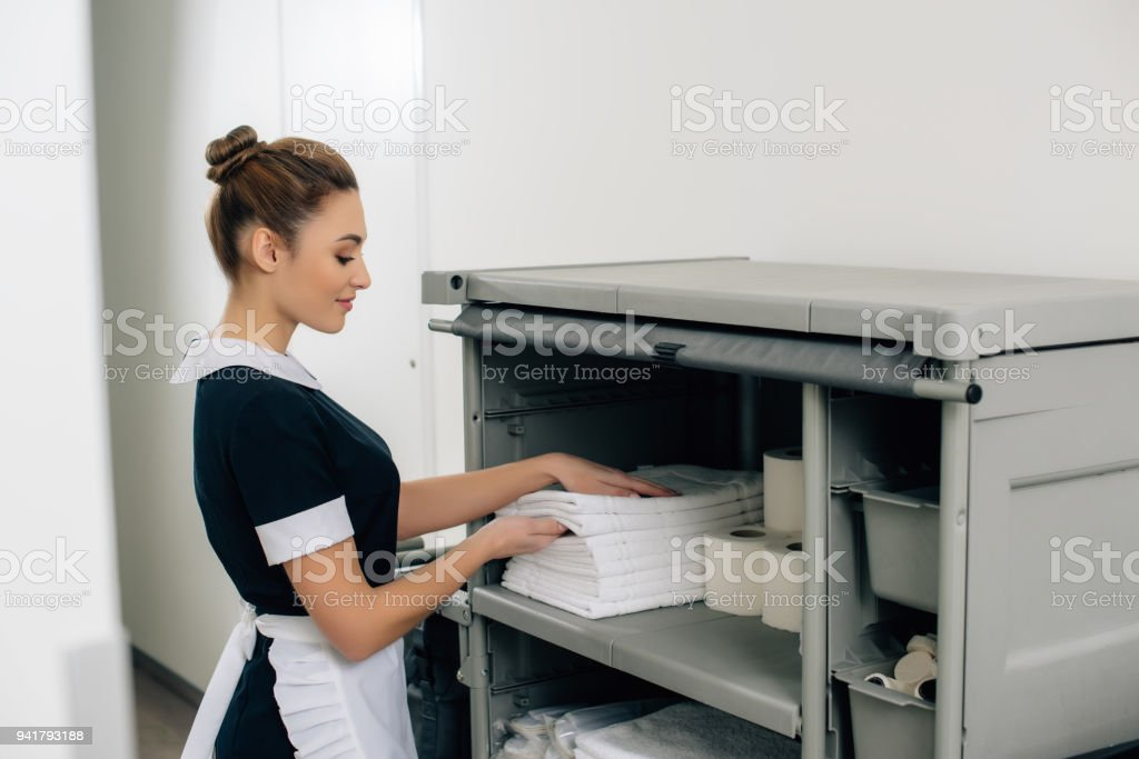 young beautiful maid in uniform taking towels from shelf of...