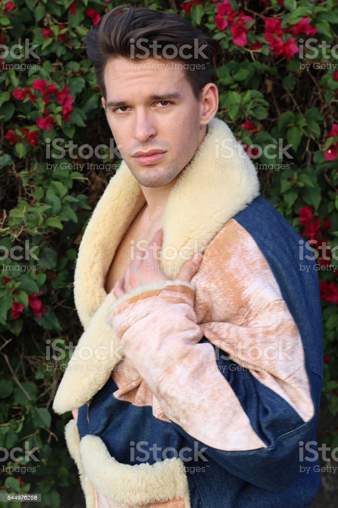 Young beautiful male in fur jacket on flowered background stock photo