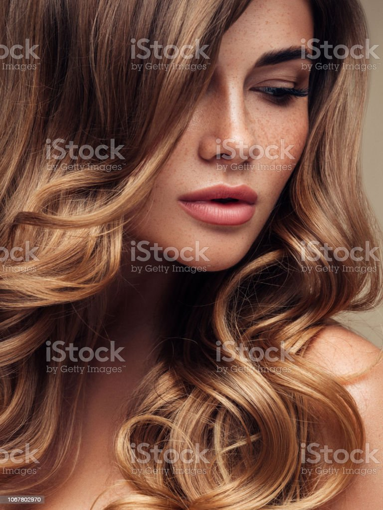 Young beautiful model with long wavy well groomed hair stock photo