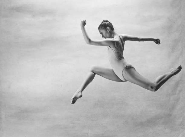 junge schöne, moderne stil tänzer springen auf einer studio-hintergrund - männliche körperkunst stock-fotos und bilder