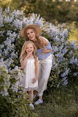 Young Beautiful Mom with Long Blonde Hair Walks in the Garden with Daughter.