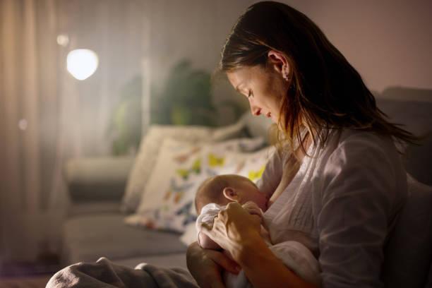 Joven hermosa madre, amamantando su bebé recién nacido en la noche - foto de stock