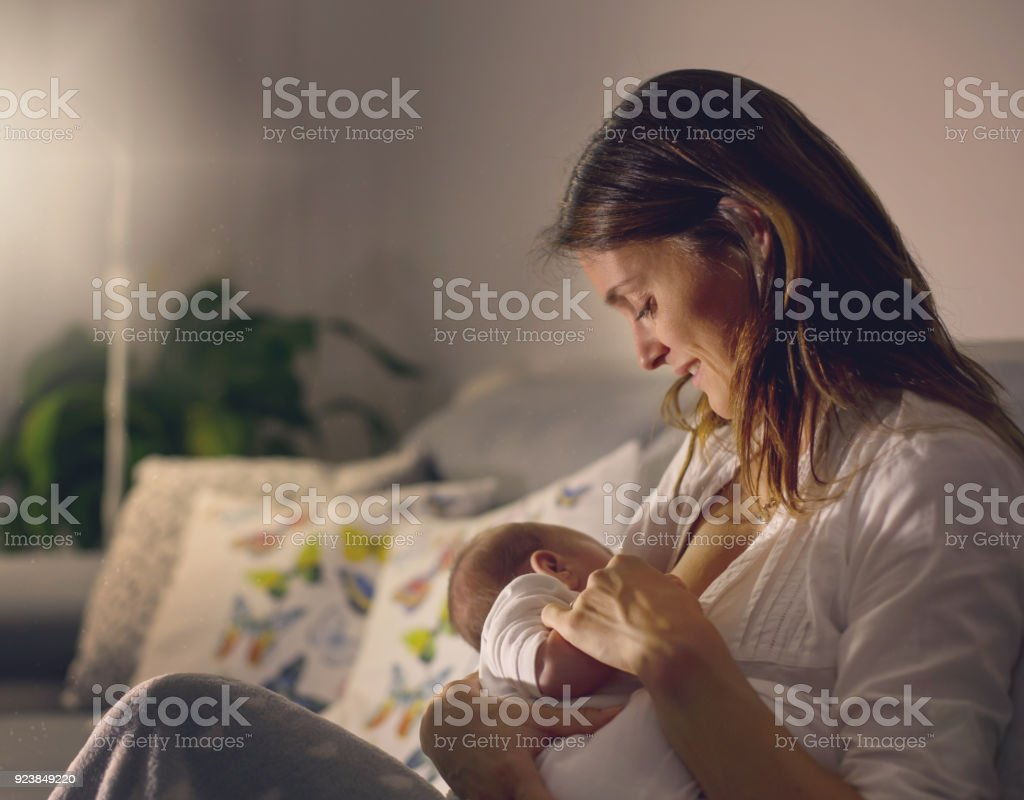Young beautiful mother, breastfeeding her newborn baby boy at night stock photo